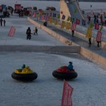 Kids enjoying ice hovercraft and a small ice slide on the Songhua River Harbin.